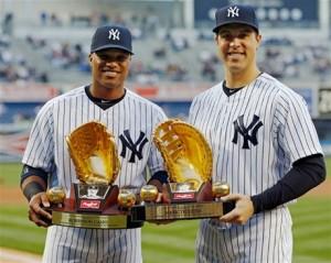 El segunda base Robinson Canó, a la izquierda y el primera base Mark Teixeira, ambos de los Yankees, posan con sus premios Guante de Oro 2012 antes de un partido de anoche.