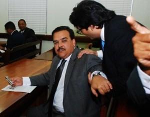 Elías Wessin Chávez habla con su abogado en el tribunal antes de anunciarse el aplazamiento de la audiencia.