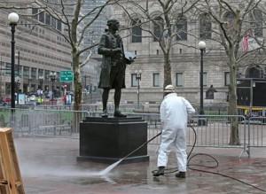 Normalidad. La escultura del pintor John Singleton Copley es lavada por un empleado de la ciudad ayer, mientras comienza la reapertura de la calle a los residentes y dueños de negocios pequeños, una semana después del doble atentado.